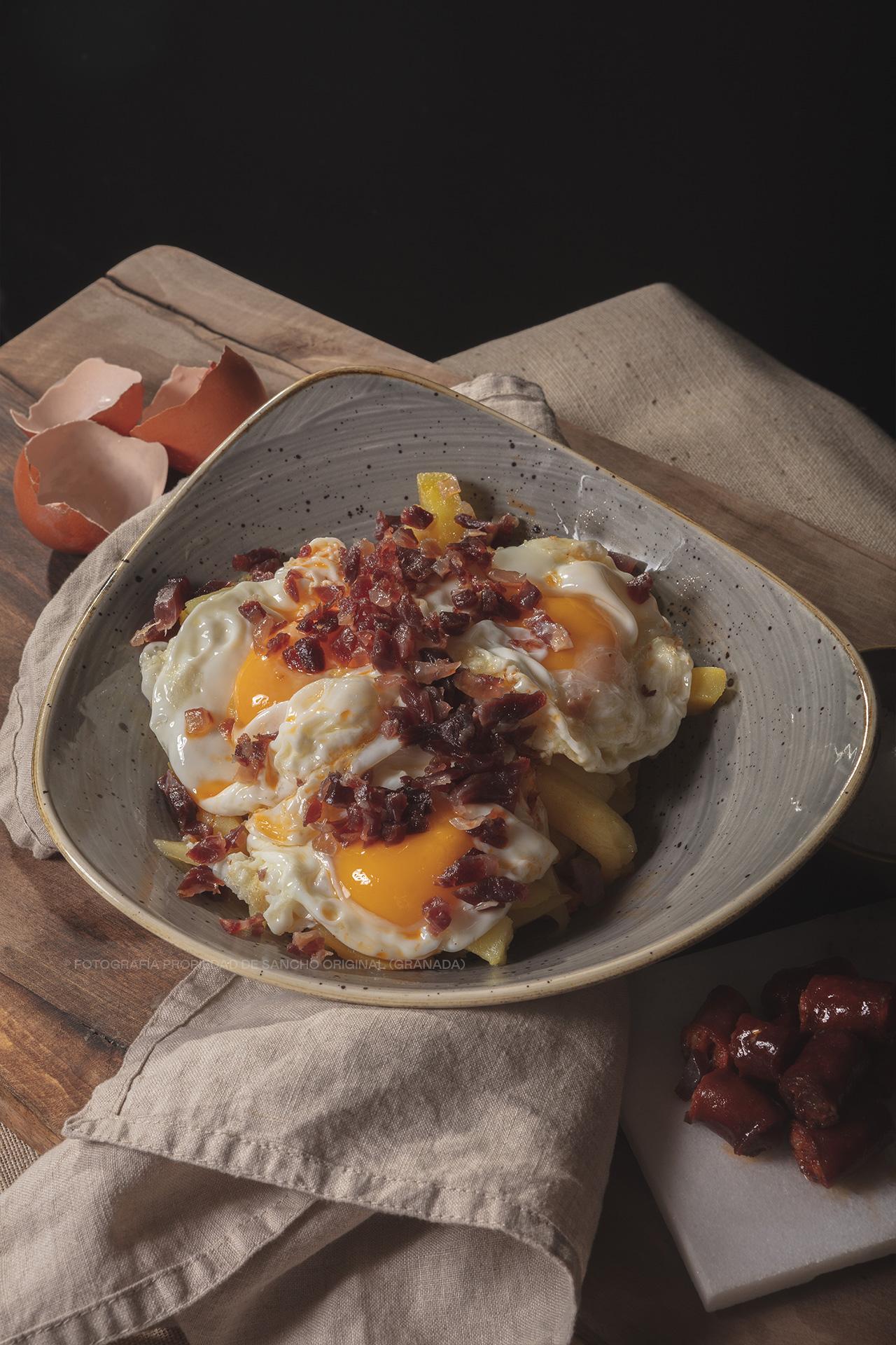 Huevos rotos con patatas, jamón serrano y chistorra de Sancho Original